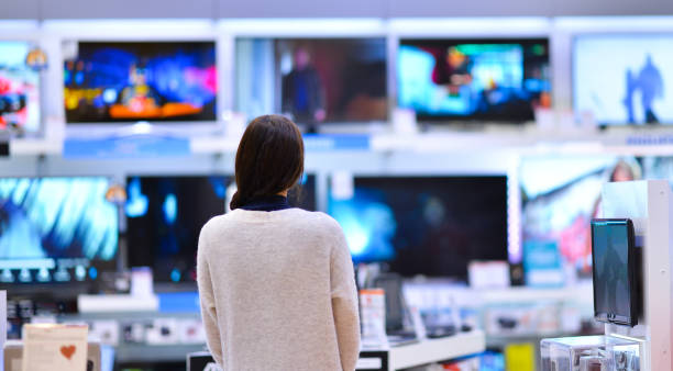 frau kauft den fernseher - freizeitelektronik stock-fotos und bilder