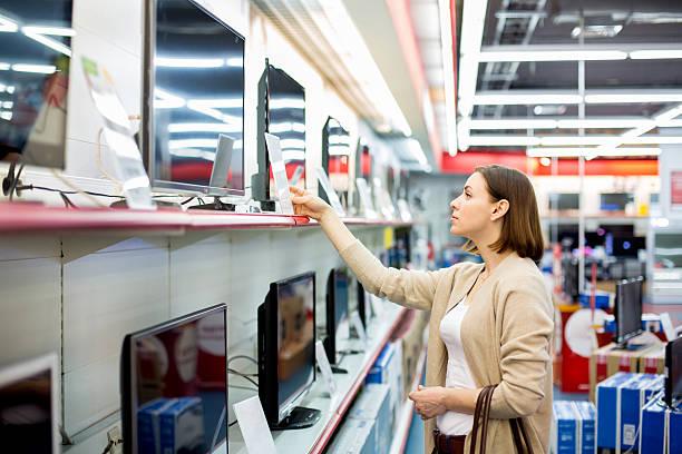 frau kauft dem fernseher - freizeitelektronik stock-fotos und bilder