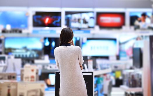 A woman looking at a wall of televisions