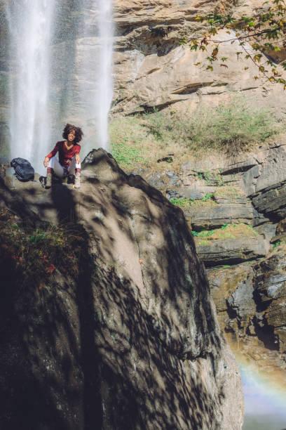 woman by a beautiful waterfall stock photo