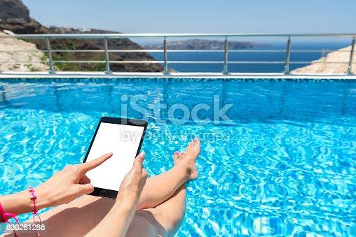 928855610istockphoto Woman by pool & blank digital tablet screen 830261288