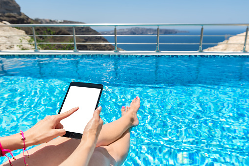 928855610 istock photo Woman by pool & blank digital tablet screen 830261288