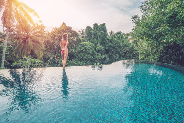 woman by the edge of an infinity pool, ubud, bali enjoying tropical climate vacations in asia - mulher natureza flores e piscina imagens e fotografias de stock