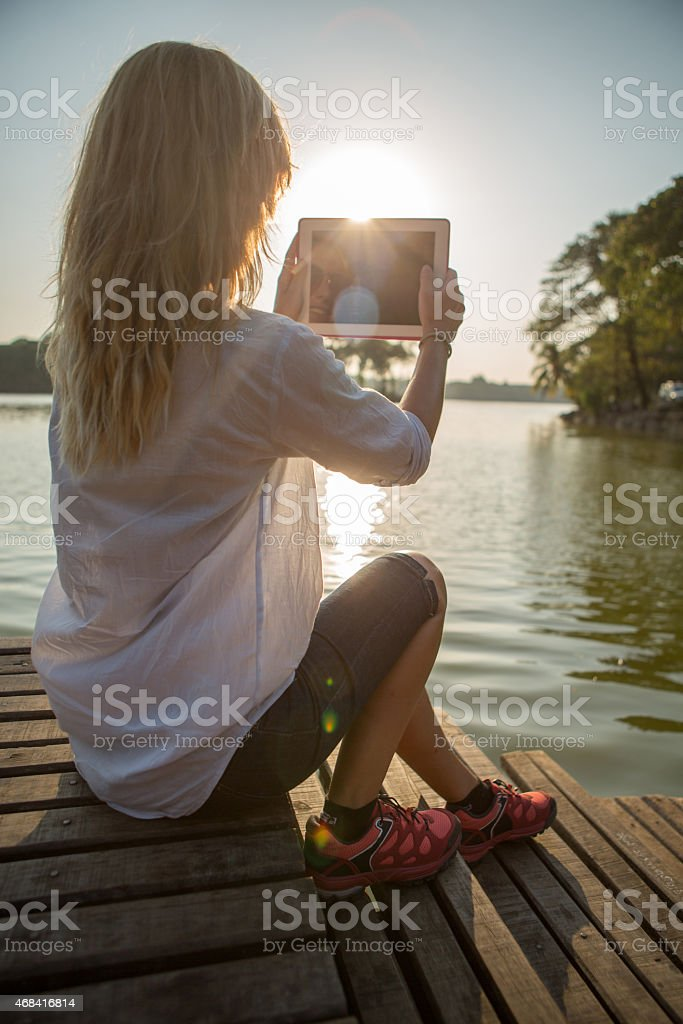 Woman by the lake taking picture using digital tablet stock photo