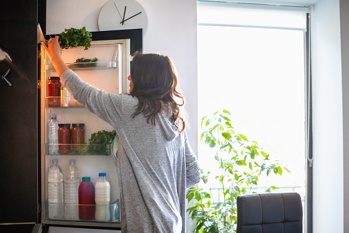 Woman holding the fridge door and taking a bunch of parsley