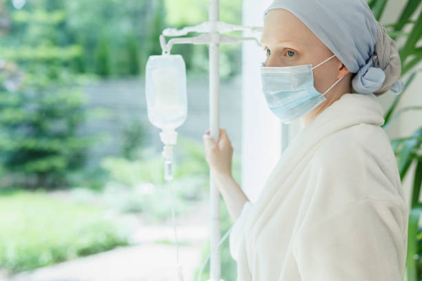 frau am fenster - chemotherapie stock-fotos und bilder