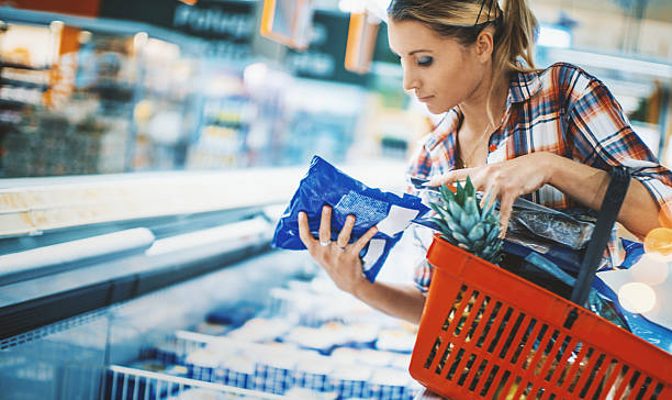 mulher andondo comida congelada em um supermercado. - comida congelada - fotografias e filmes do acervo