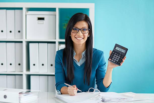 Mujer calcula el impuesto en escritorio de oficina - foto de stock