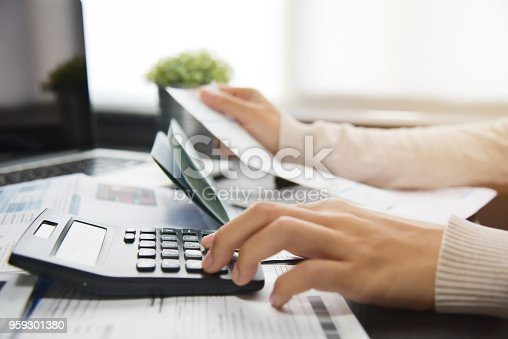 Close up of woman hand calculating her monthly expenses with calculator.  Debt.
