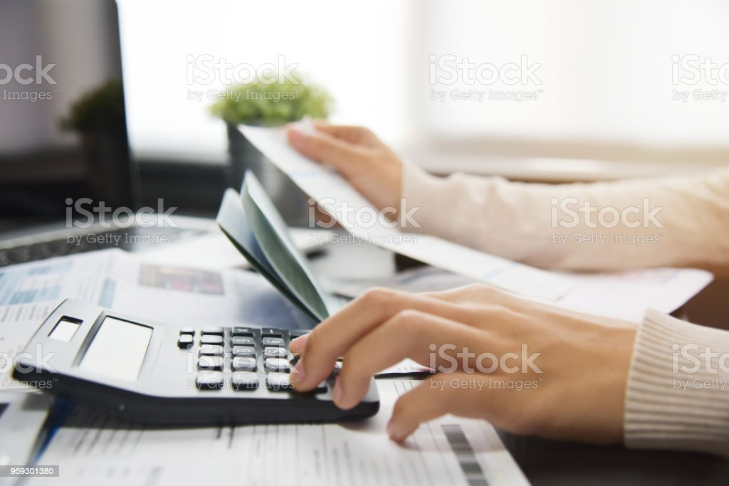 Woman calculating her Debt. stock photo