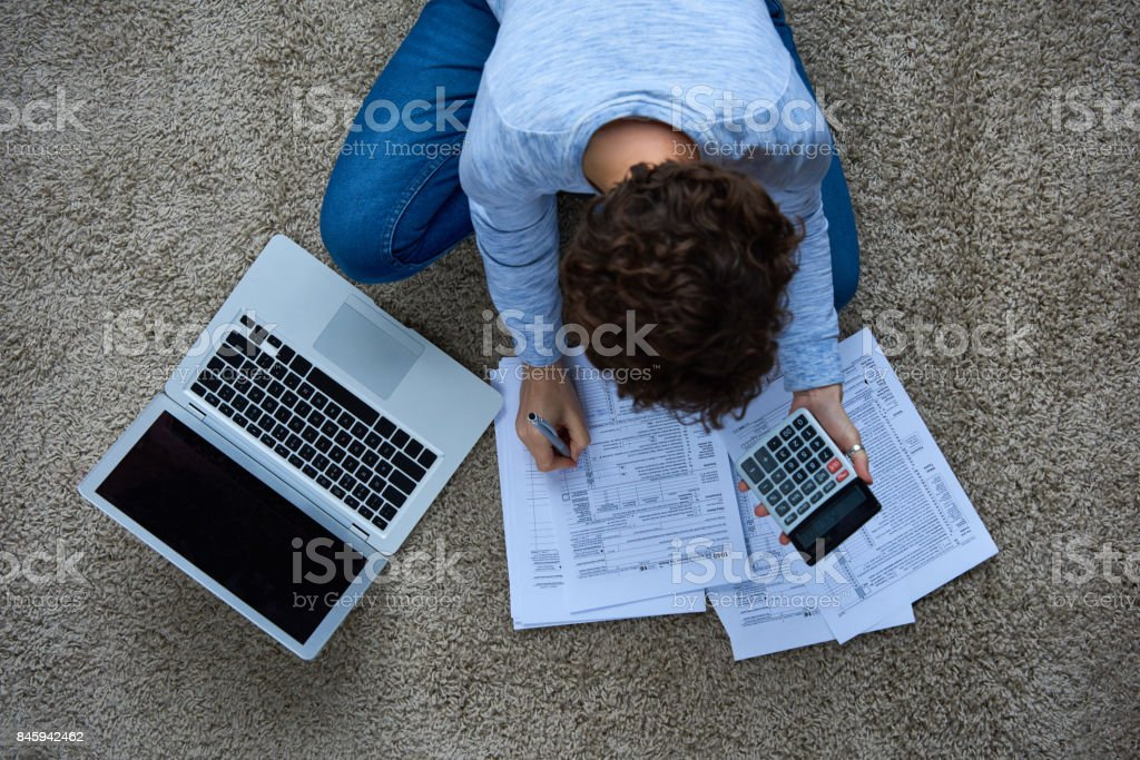 Woman calculating taxes at home stock photo
