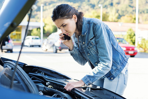 Young woman calling a car assistance service with her smartphone, her car has broken down