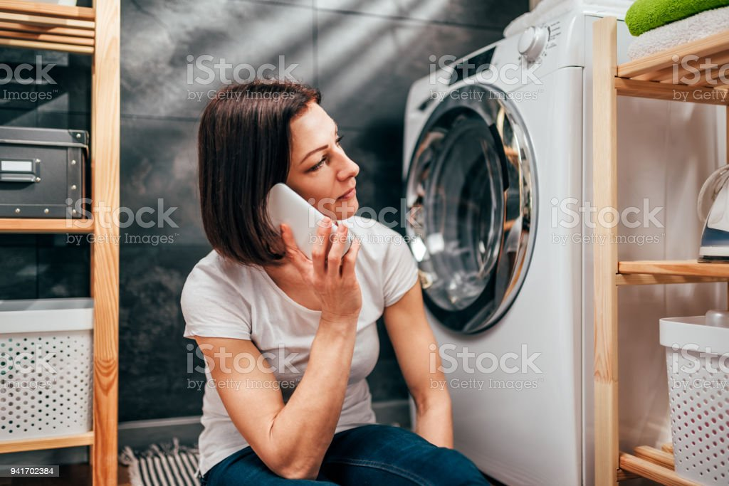 Woman calling for appliance repair service stock photo