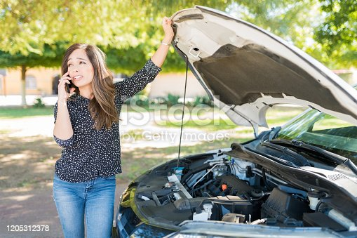 Woman talking on mobile phone while standing by broke down car at roadside