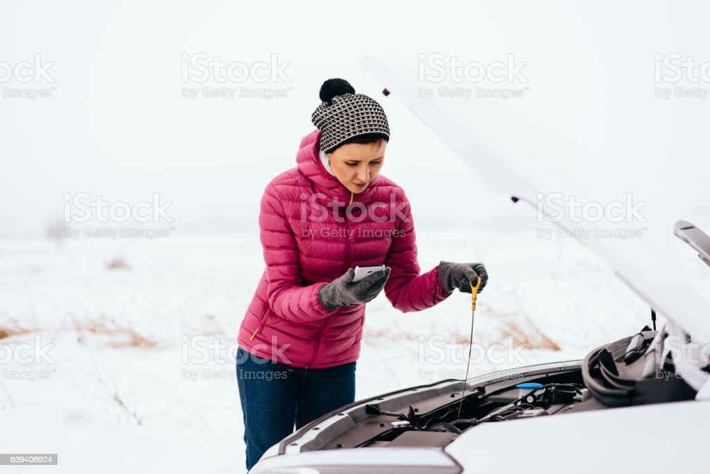 Woman calling for help or assistance - winter car breakdown stock photo