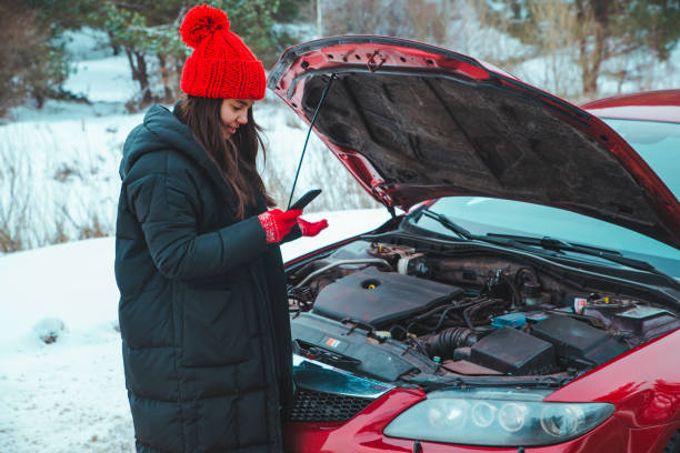 woman calling for help with broken down car at winter highway stopped at roadside stock photo