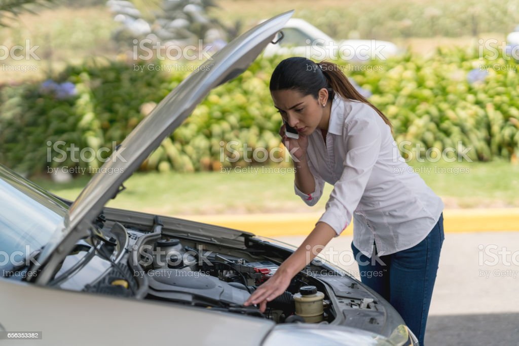 Woman calling her insurance after a car breakdown stock photo