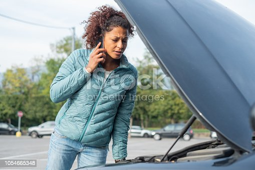 860373412 istock photo Woman calling mechanic service after vehicle problem 1054665348