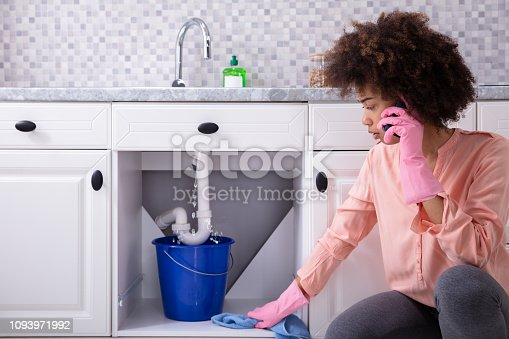 Young Woman Wearing Pink Gloves In Hand Calling Plumber In Front Of Leaking Sink Pipe