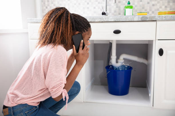 Woman Calling Plumber In Front Of Leaking Sink Pipe Young Woman Calling Plumber Crouching In Front Of Water Leaking From Sink Pipe accidents and disasters stock pictures, royalty-free photos & images