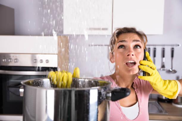 frau berufung klempner, wasser austritt von decke zu beheben - telefonschrank stock-fotos und bilder