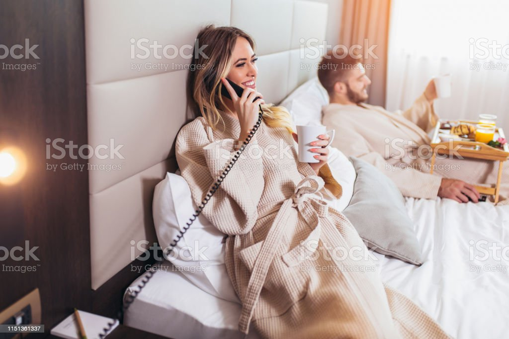 Woman calling room service for food from hotel room
