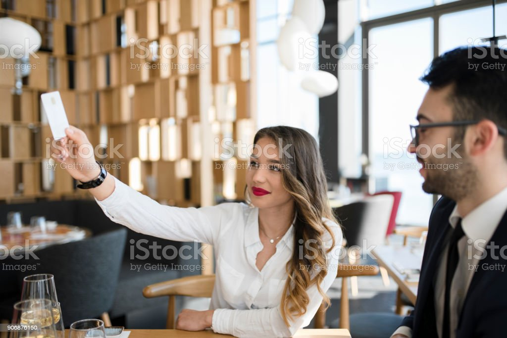 Woman calling waiter to pay for lunch stock photo