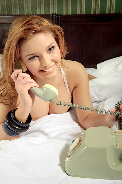 Woman calling with an old phone stock photo