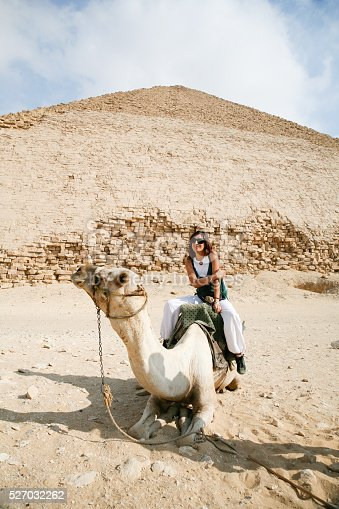 883177796istockphoto woman camel and pyramid 527032262