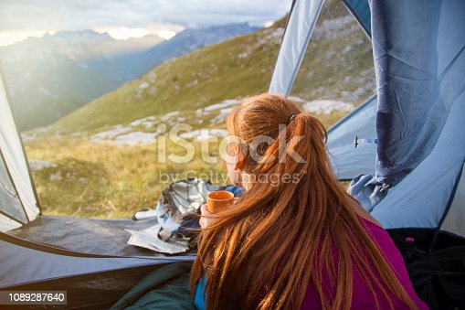 Young woman lying inside a tent with a cup of tea in her hands and watching sunrise in the high mountains.