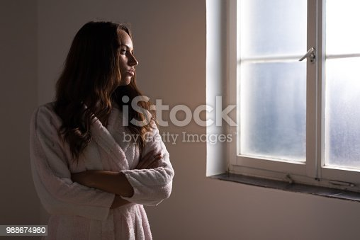 Woman sufering from cancer looking through hospital window.