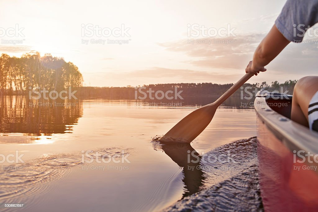 Woman canoeing at sunset royalty-free stock photo