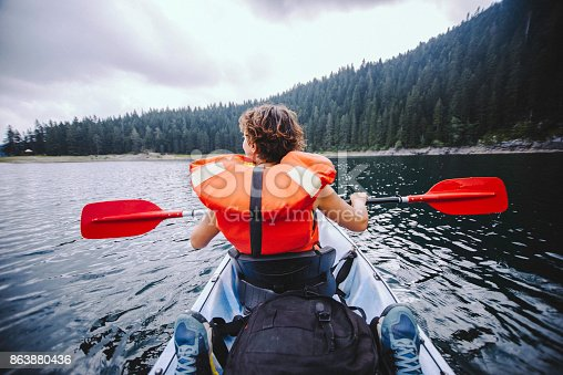 Photo of a woman canoeing in the lake, shooted from the back.