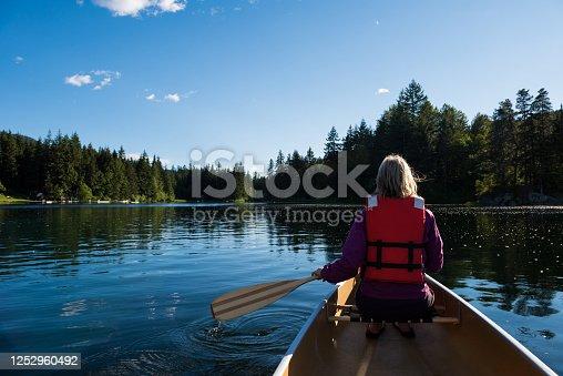 istock Woman canoeing on a mountain lake 1252960492
