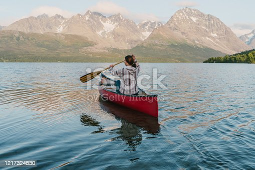 Young Caucasian woman canoeing  on fjord in Norway