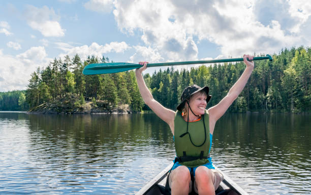 Woman canoeing on the lake stock photo