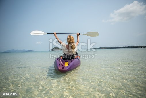 istock Woman canoeing raising paddle for success 466479050