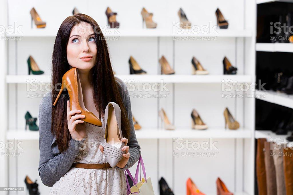 Woman can't choose stylish pumps stock photo