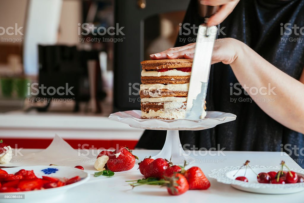 Woman Carefully Icing The Cake stock photo