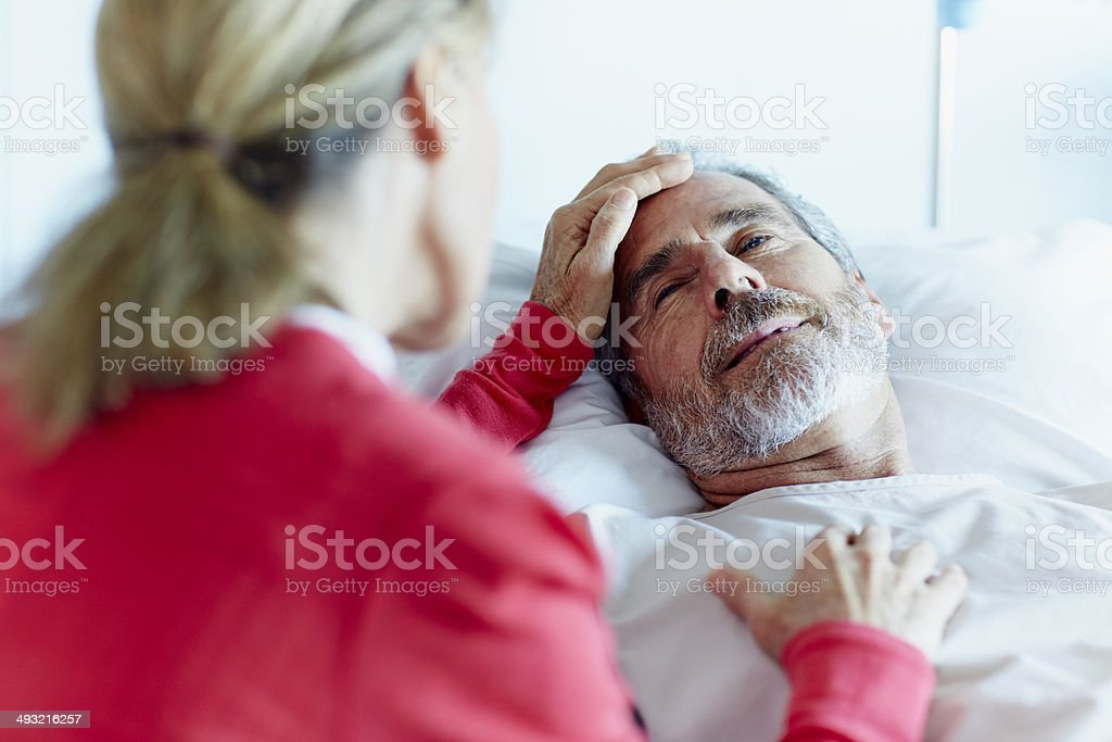 Woman caressing ill man in hospital ward stock photo