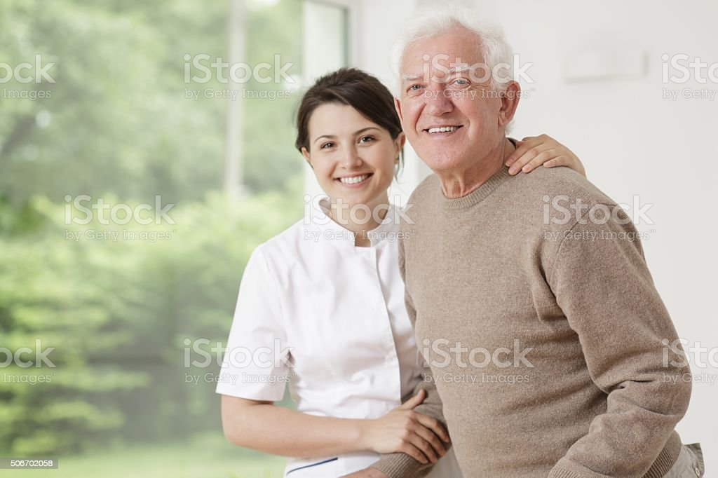 Woman caring for old man stock photo