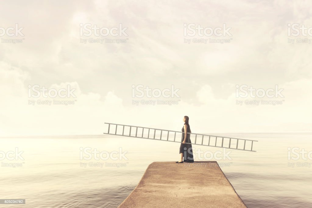 Woman carries a long ladder to climb into the sky stock photo