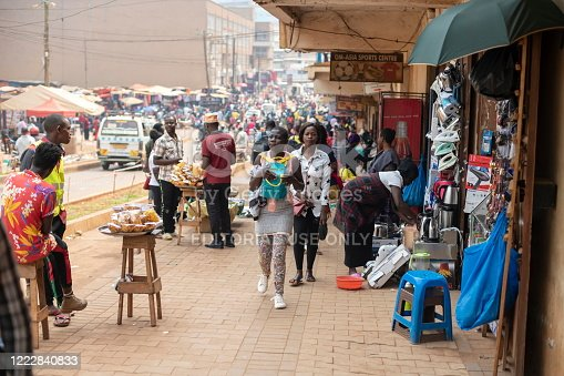 Kampala, Uganda - January 12th, 2020: Unidentified woman carries her backpack on a chest along a street of Kampala, Uganda. Carrying backpacks in front is common practice to prevent pickpocketing.
