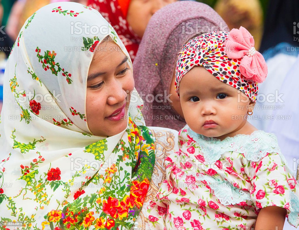 Woman carries child in Jakarta, Indonesia during Ramadan celebration. stock photo