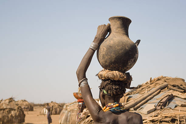 Woman carries on her head a container with water, Ethiopia stock photo