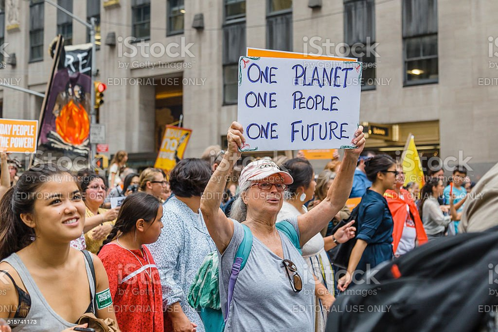 Woman carries placard during the 2014 People's Climate March, NYC. royalty-free stock photo