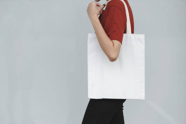woman carry bag on gray background in save earth concept or say no plastic bag. - tote bag imagens e fotografias de stock