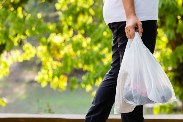 Woman Carry Plastic Bags Closeup woman carry the grocery plastic bags while walking in the forest park, environment concept plastic bag stock pictures, royalty-free photos & images
