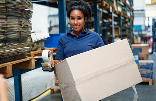 Woman carrying a cardboard box in a warehouse