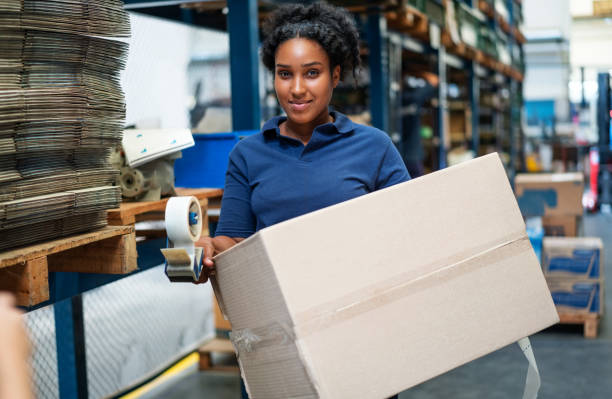 Woman carrying a cardboard box in a warehouse stock photo